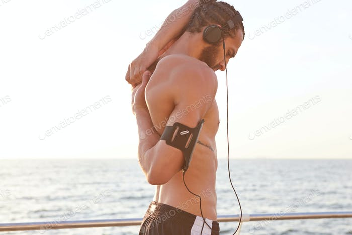Young sporty handsome bearded guy enjoy the morning , does stretching