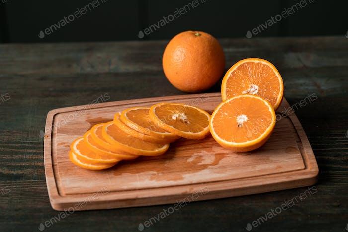 Gruppe von frischen Orangenscheiben und Hälften der Früchte auf Holzschneidebrett