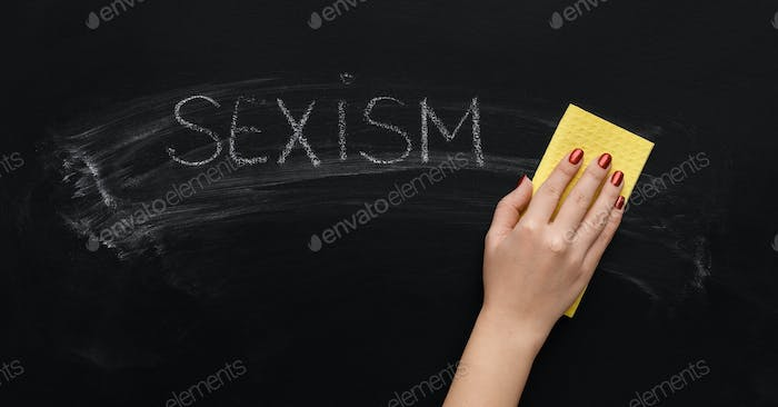 Sexism written on chalkboard and hand with sponge
