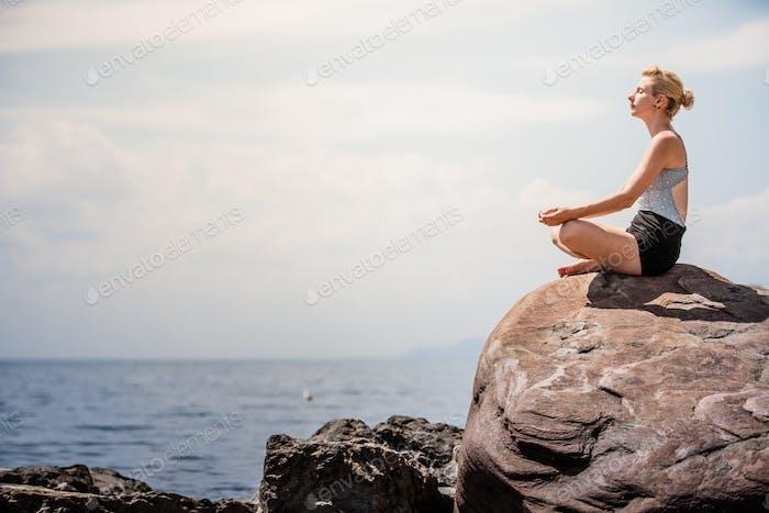 Young Woman doing Lotus Yoga Position
