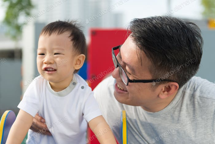 Asian father with his little boy at playground
