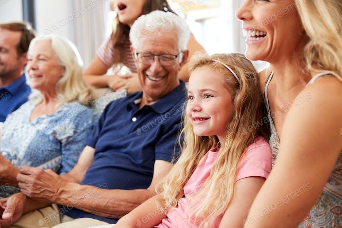 Multi-Generation Familie sitzen auf Sofa zu Hause beobachten Film zusammen
