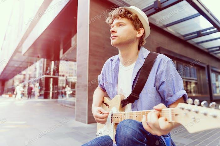 Junge Musiker mit Gitarre in der Stadt
