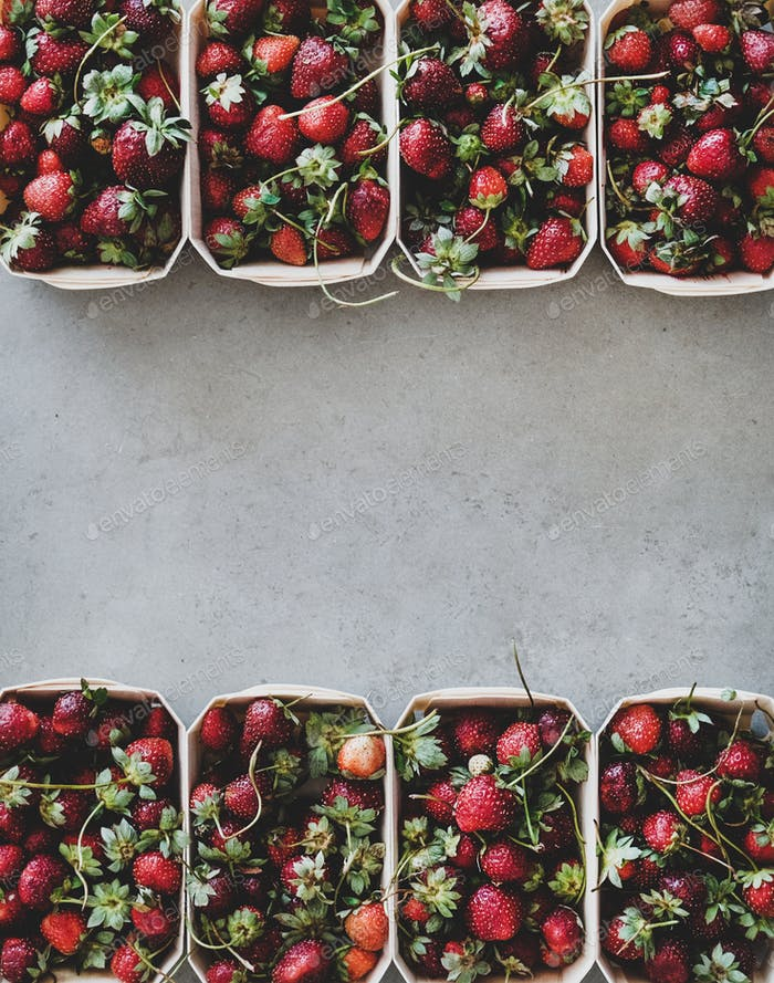 Fresh strawberries in plastic-free boxes over concrete background, copy space