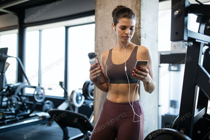 Young smiling woman at the gym relaxing and listening to music using a mobile phone