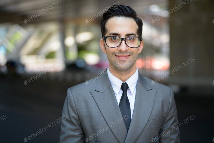 Face of happy young handsome Persian businessman in the city streets outdoors