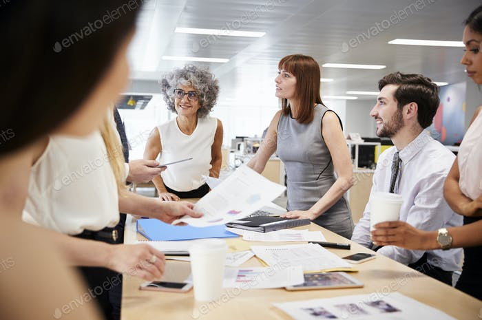 Group of business colleagues brainstorm in open plan office