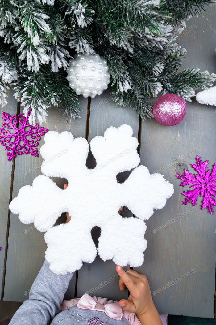 Christmas decoration. Child hand with decorative snowlake. Top view.