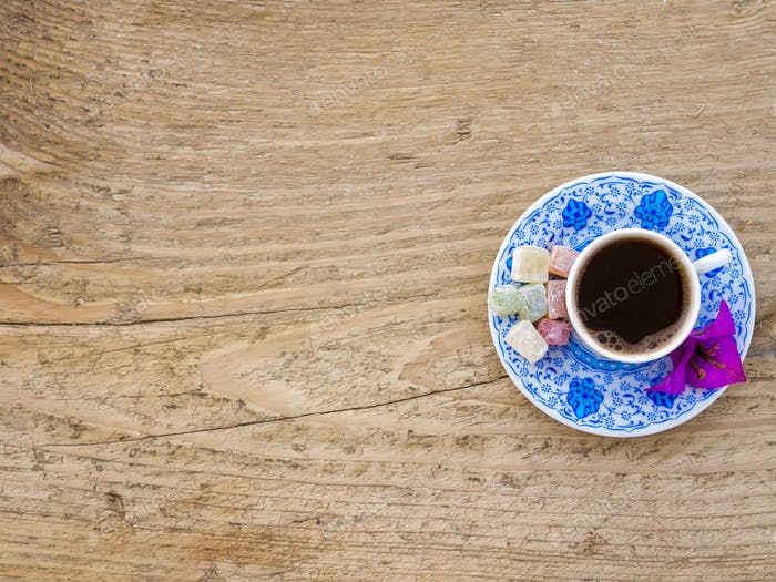 A cup of Turkish coffee with sweets and spices on a wooden surfa