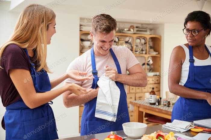 Man kämpft, um Flasche zu öffnen, als Studenten Zutaten für Gericht in der Küche Kochkurs vorbereiten