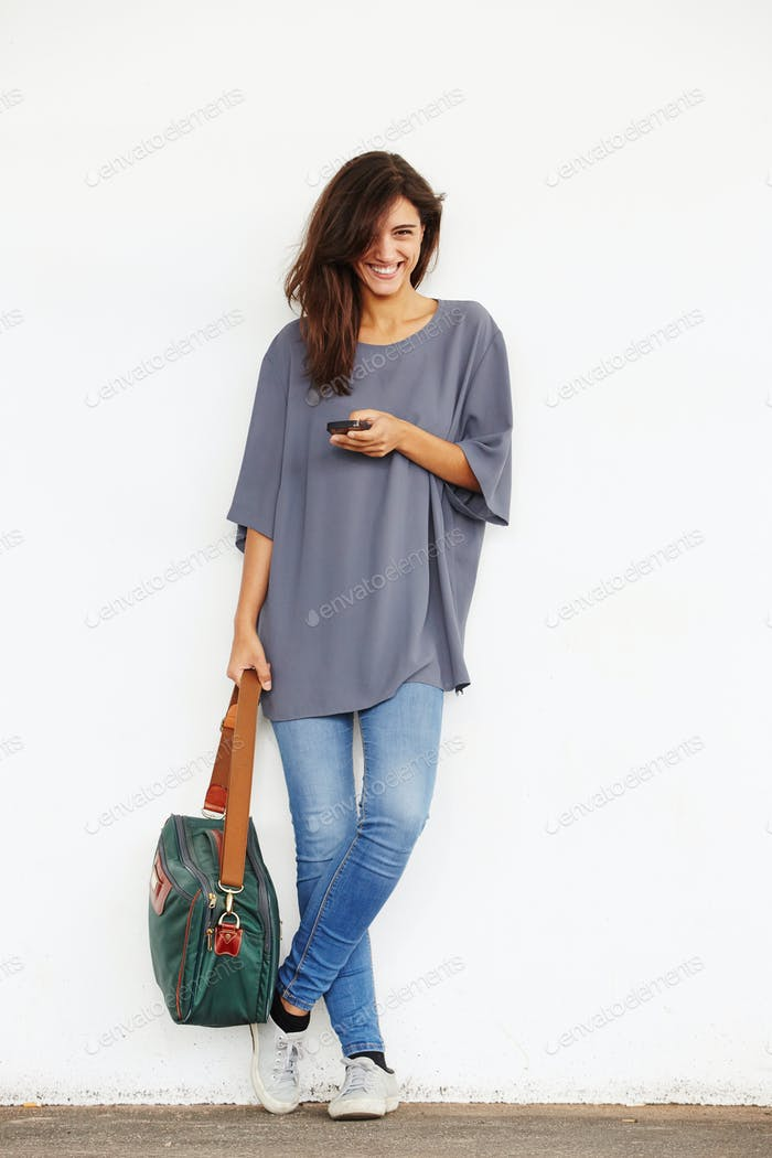 happy young woman standing outside with mobile phone and bag