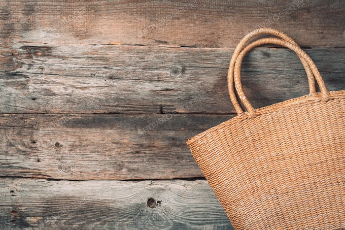 Handmade summer bag on wooden background. Top view. Fashionable stylish accessory. Natural, organic