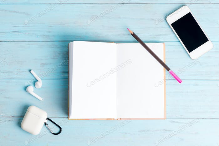Paper notebook for notes, modern smartphone and earphones on a light blue wooden background. Top