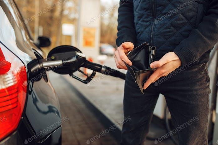 Mann mit leerer Geldbörse auf Tankstelle, Kraftstofffüllung