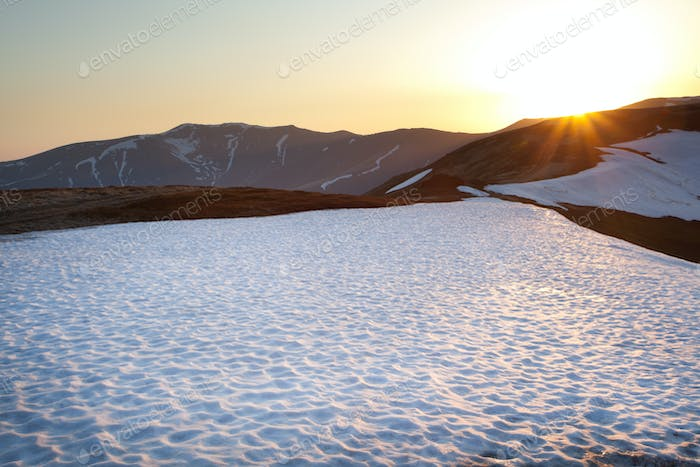 Mountain with snow and grass, sunny weather