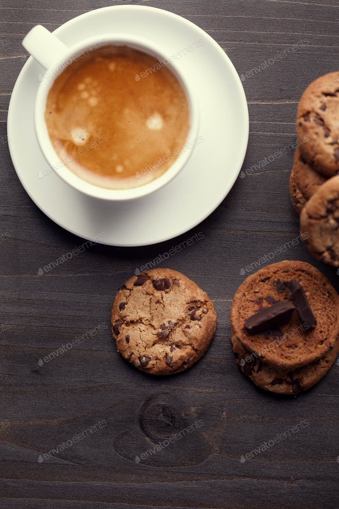 Homemade chocolate chip cookies and a cup of coffee on dark old wooden table