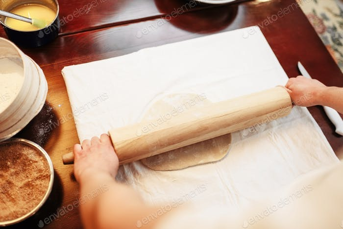 Chef roll out the dough with rolling pin, top view