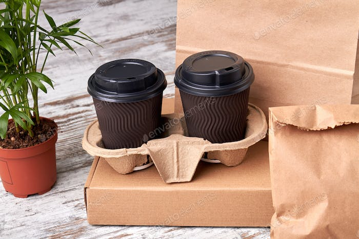 Two closed paper cups of coffee in cupholder.