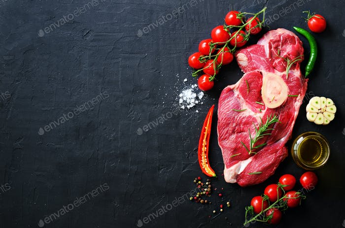 Raw meat steaks with cherry tomatoes, hot pepper, garlic, oil and herbs on dark stone, concrete