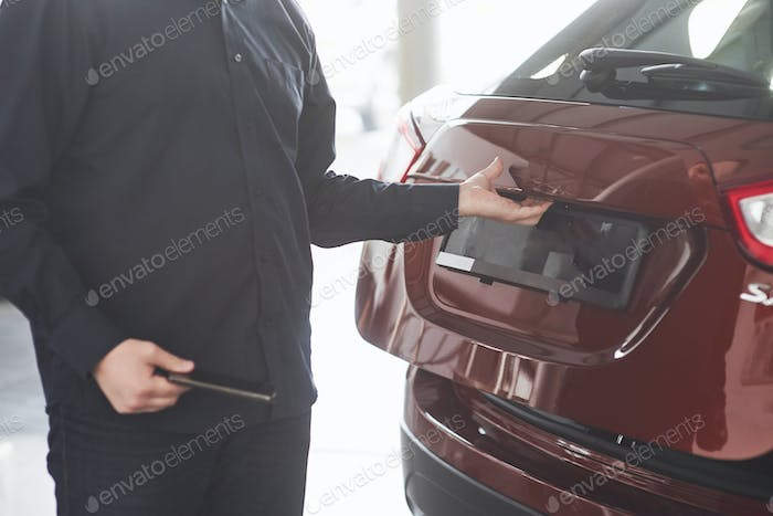 Rear part of vehicle. Man in official clothes stands near his new car in automobile salon