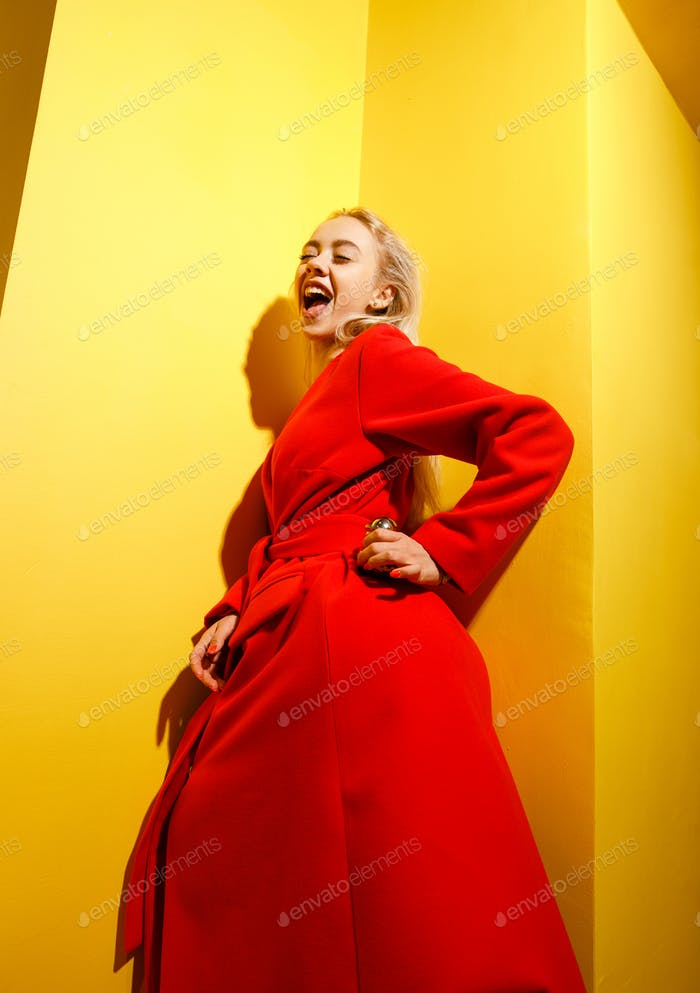 Fashion young girl blogger dressed in stylish red coat poses with the gold little duck figurine in