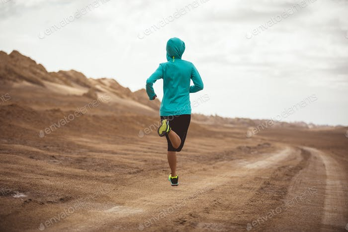 Fitness woman trail runner cross country running  on sand desert