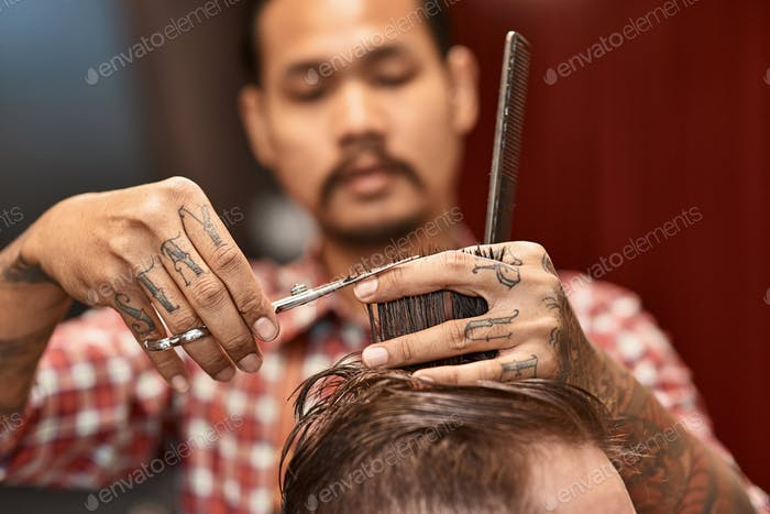 Close up of scissors in hands of a masterful thai hairdresser