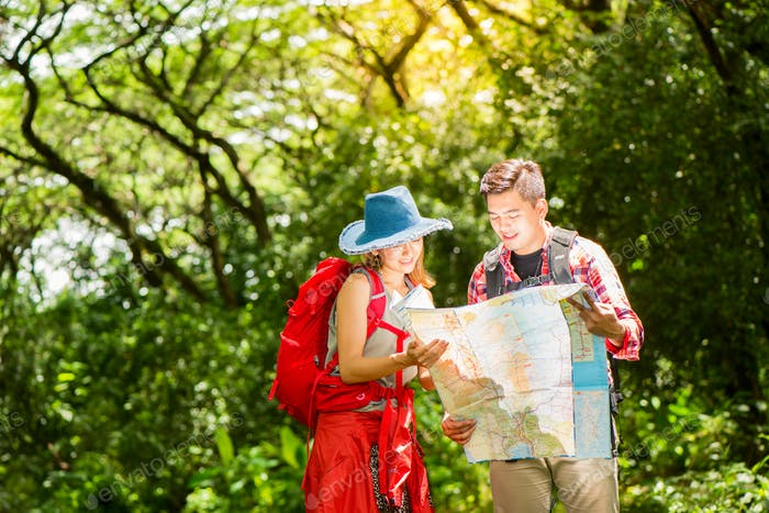 Couple or friends navigating together smiling happy during camping travel.
