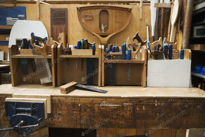 Work bench in a boat-builder's workshop, selection of hand tools for wood working.