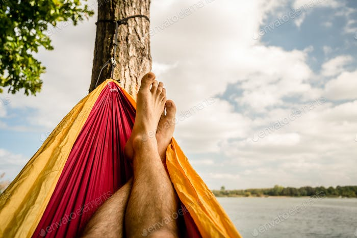 Relaxing in the hammock at the beach under trees, summer day