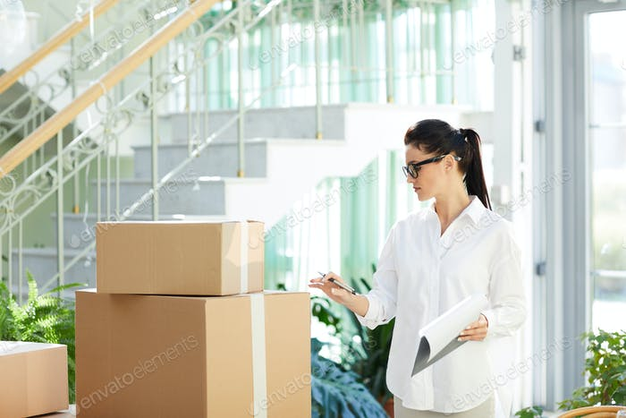 Confident entrepreneur viewing packaged goods