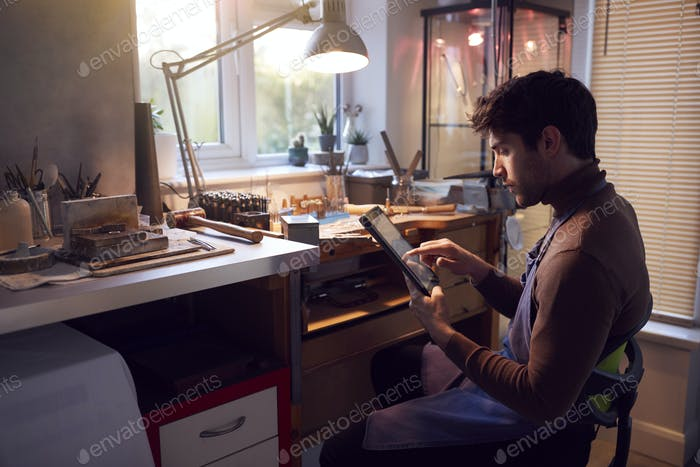 Male Jeweller Looking At Ring Design On Digital Tablet In Studio