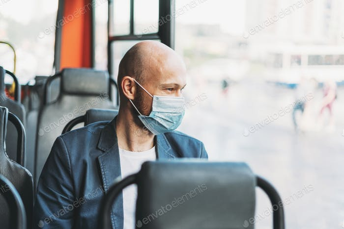 Adult bald bearded man in medical face mask looking out the window in bus
