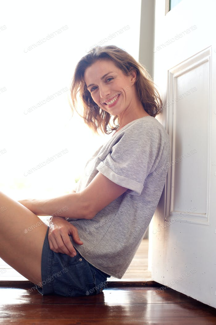 Relaxed smiling woman sitting on wooden floor at home