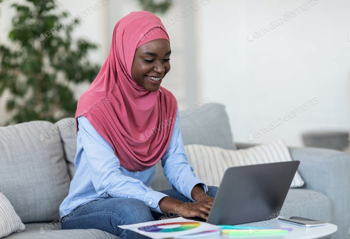 Freiberufliche Karriere. Moderne schwarze muslimische Dame in Hijab Arbeiten An Laptop Zu Hause