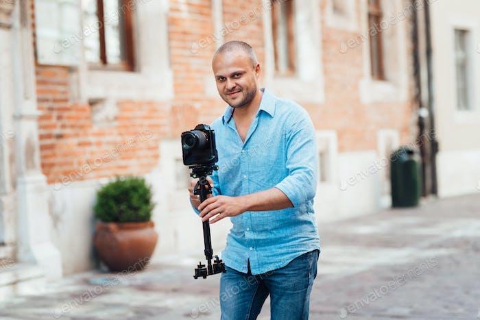 junger Kerl, Fotograf zu Fuß in den alten Straßen Europas