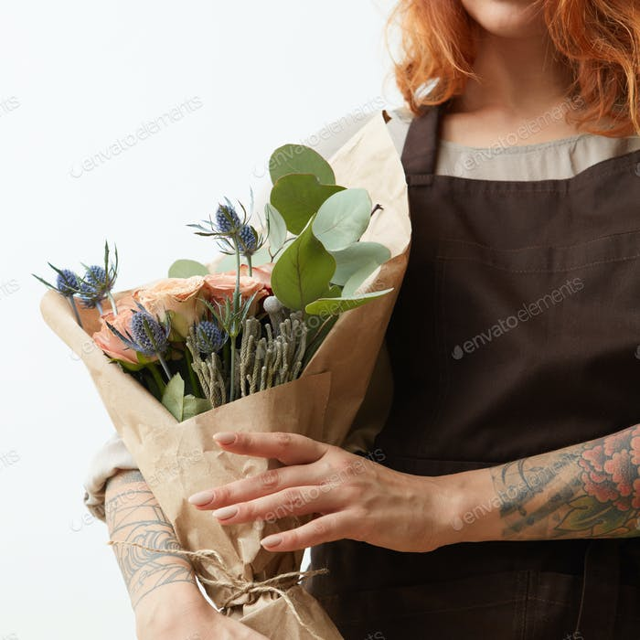 Young girl with ginger hair hold beautiful bunch with fresh natural flowers and leaves on a light