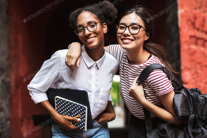 Two pretty smiling girls in eyeglasses with laptop and backpack