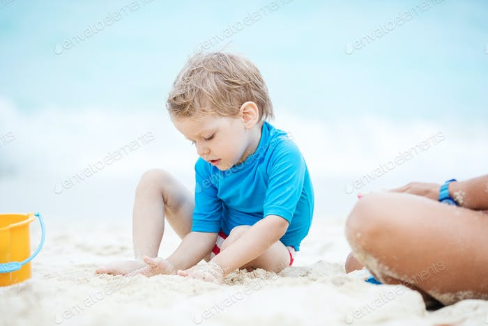 Cute little boy playing with sand on the beach