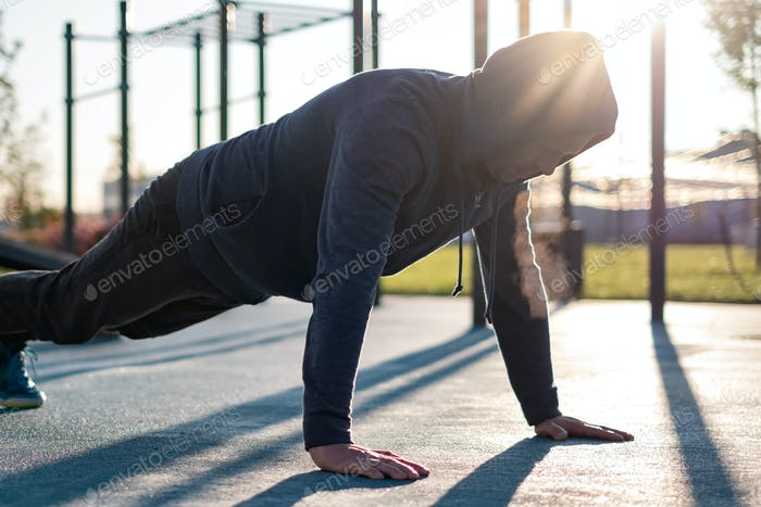 Young man doing push ups or plank exercise in the morning