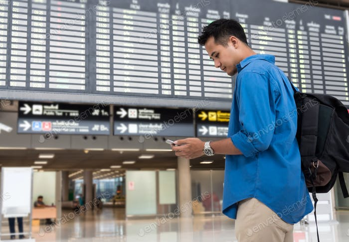 Asian traveler using the smart mobile phone for check-in at the flight information screen