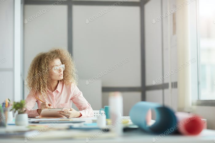 Creative Young Woman Daydreaming at Workplace