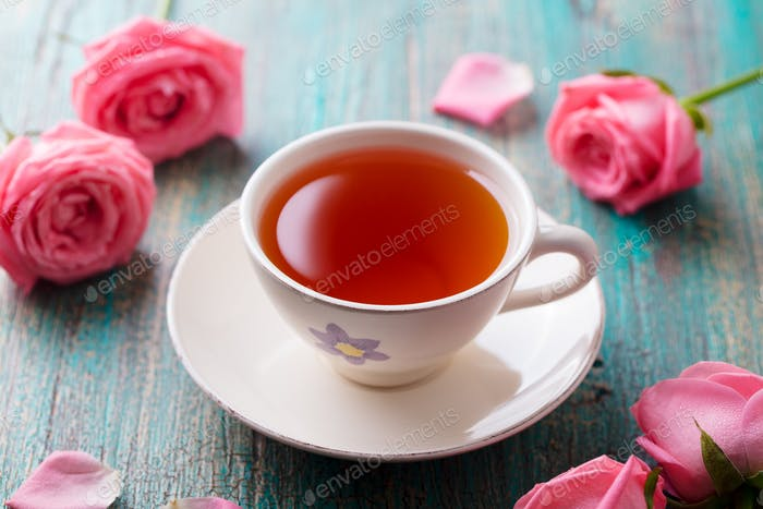 Cup of Tea with Pink Rose. Colorful Turquoise Wooden Background. Close up.