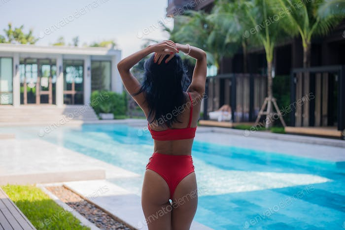 Young sexy woman in swimsuit stand near poolside wearing sunglasses at luxury hotel