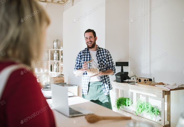 Young shop assistant serving a woman in a zero waste shop.