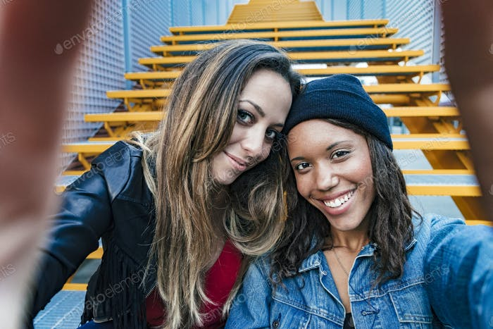zwei gemischte Rasse weibliche Freunde sitzen und nehmen ein selfie