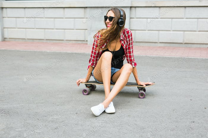 Young woman sitting on the skater. Smiling woman with skateboard in outdoors