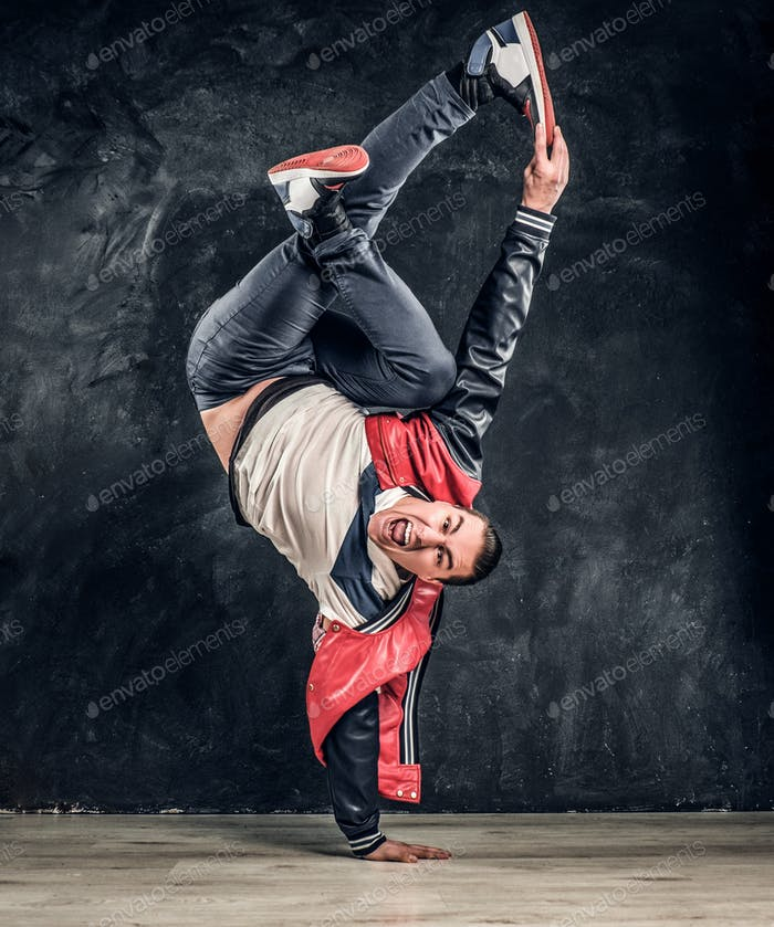 Emotional stylish dressed man performing break dance moves on the floor.