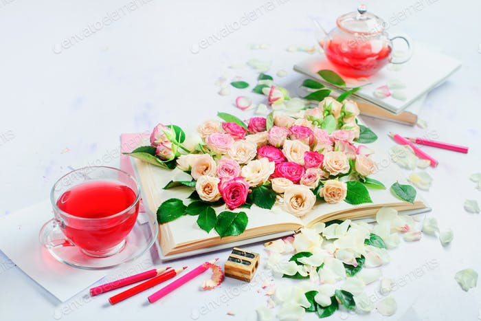 Header with an open book on a white background with flowers, rose petals, pink stationery and herbal
