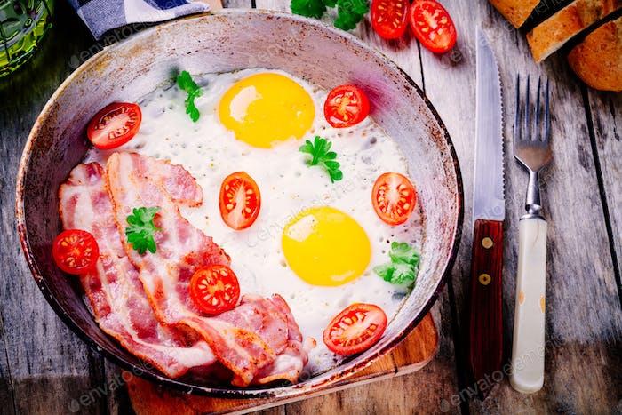 Frühstück mit Spiegeleier, Speck, Tomaten und Petersilie